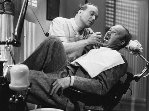 Пациент в стомтаологическом кресле со страхом в глазах смотрит на врача