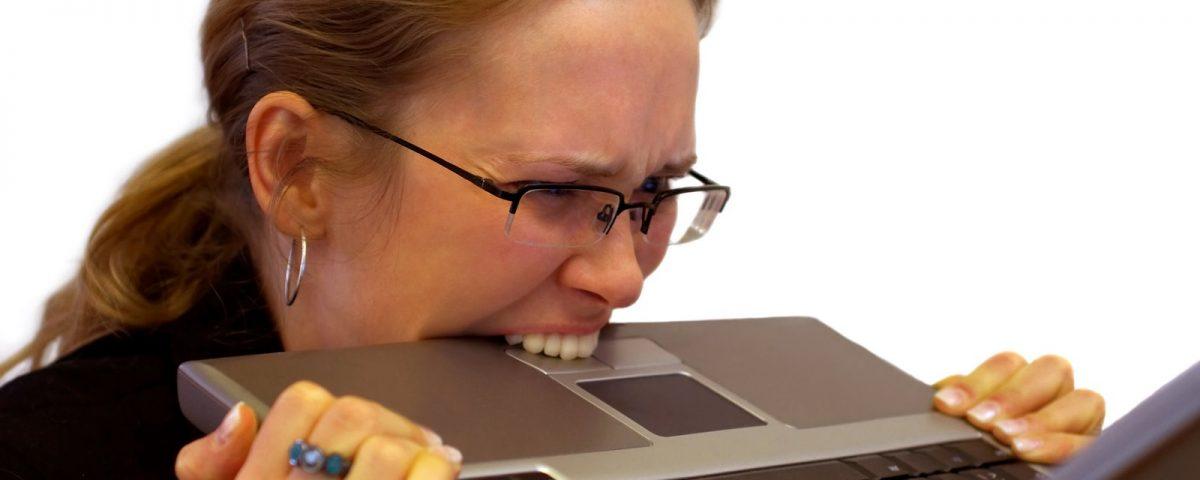 Женщина в состоянии повышенного нервного напряжения пытается укусить ноутбук